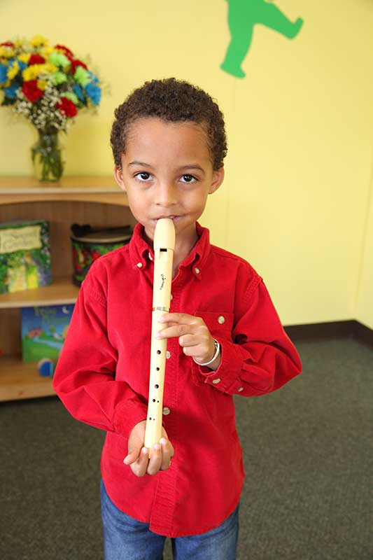 Young boy playing a recorder in a Young Child Year 2 class.