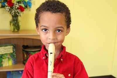 Young boy playing a recorder in a Level 5 class.