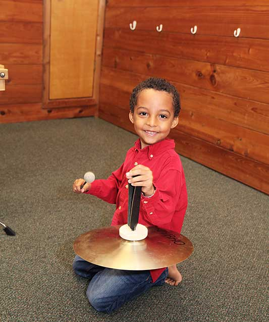 Young boy playing a cymbal in Kindermusik class.